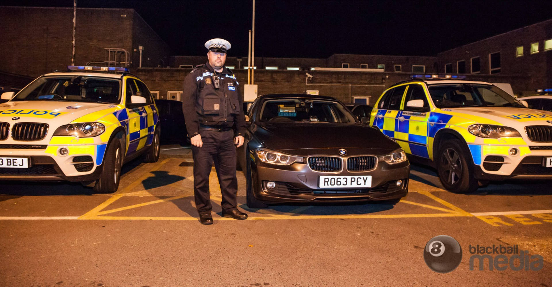 United Kingdom police officer standing next to unmarked police cruiser